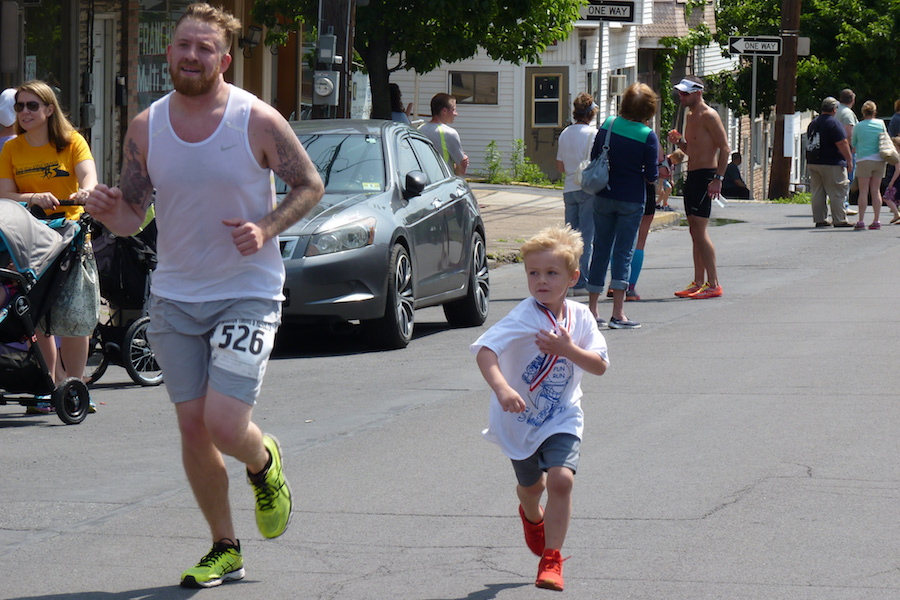 Photo of a child attempting to keep up with runners finishing the summer 2017 Coal Cracker 10K race in downtown Shenandoah on June 10. Photo by David Lindenmuth.