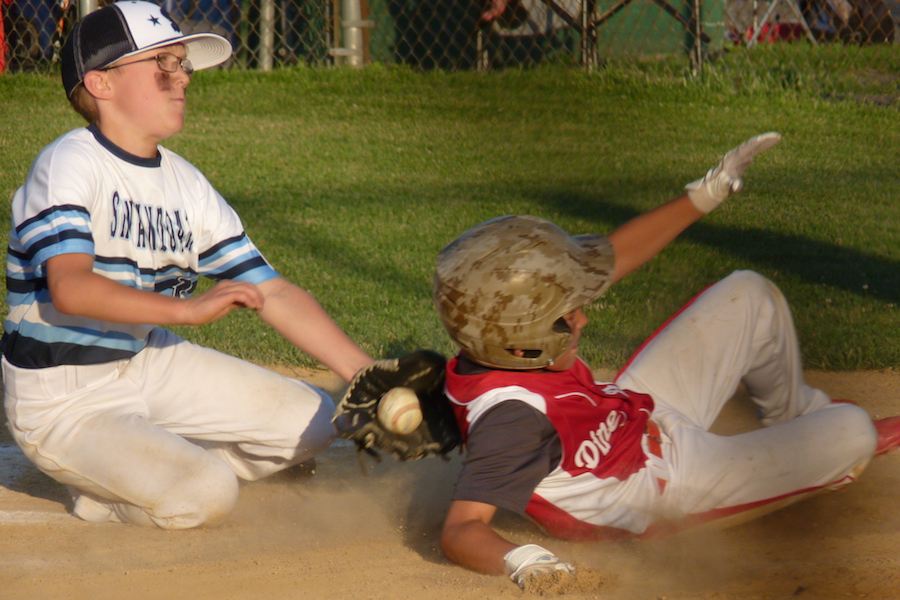 Photo of a little league baseball all star attempting to tag a sliding player out at home plate.
