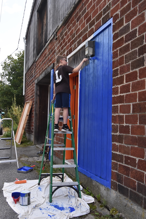 Photo of Jack Rhoades on a ladder painting the Coal Cracker Kids headquarters.